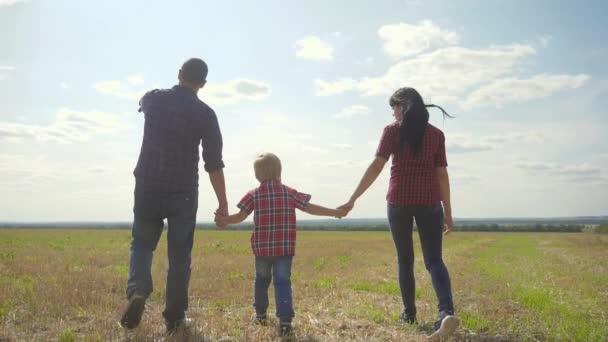 glücklich Familie Wandern Natur Teamwork Freundschaft Pflege Konzept Zeitlupe Video. Vater, Mutter und Sohn gehen in der Natur spazieren und halten sich an der Hand. glückliche Familieneltern Mann und Mädchen halten kleinen Jungen