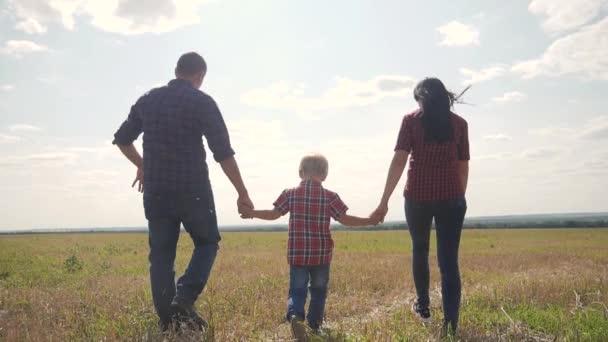 glücklich Lifestyle Familie Wandern Natur Teamarbeit Freundschaft Pflege Konzept Zeitlupe Video. Vater, Mutter und Sohn gehen in der Natur bei Sonnenuntergang Hand in Hand. glückliche Familieneltern Mann und Mädchen halten kleinen Jungen