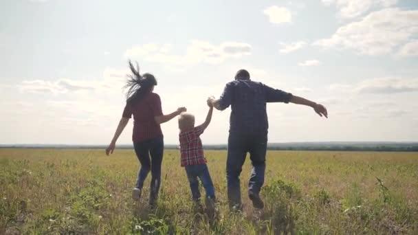 šťastná rodina provozuje přírodu teampráce přátelství péče koncept pomalý pohyb video. otec mamka a syn, kteří běží v přírodě sluneční svit se drží za ruku. šťastné rodinné rodiče muž a dívka drží malého chlapce běhat
