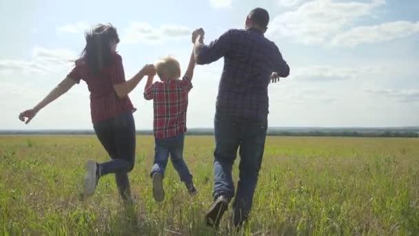 glückliche Familie betreibt Natur Teamwork Freundschaft Pflegekonzept Zeitlupe Video. Vater Mutter und Sohn, die in der Natur bei Sonnenuntergang laufen, halten sich an der Hand. Lebensstil glückliche Familie Eltern Mann und Mädchen halten kleinen Jungen