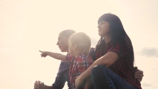 šťastný rodinný kolega koncept pomalý pohyb životní styl video. otec mamka a syn silueta sedí venku na slunci. Otče muž objetí máma a syn se v dálce ukazují, že šťastná rodina