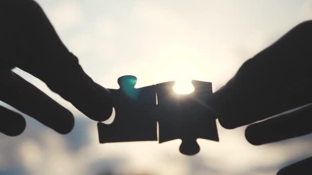 koncepce podnikových financí. mužské ručičky spojují dvě hádanky s siluetou života na slunci. symbol spolupráce mezi přidružením a připojením. strategie podnikání