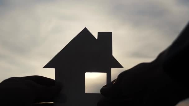 happy family house lifestyle construction concept. man holding home a paper house in his hands at sunset silhouette sunlight. ecology life video symbol