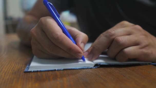 lifestyle man writes in notebook. mans hand writing in a notepad. concept business education. man makes notes in notebook that lies on the table