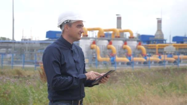 Teamwork Tankstellenkonzept. Der Ingenieur steht und schreibt Dokumente auf einen weißen Schutzhelm mit digitalem Tablet. Mann Ingenieur in Lifestyle-Helm arbeiten am Bahnhof studieren auf Gas