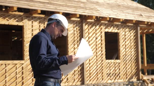 concept building constructing architect slow motion video. man builder in a helmet stands at a construction holding a scheme house plan. site near lifestyle a wooden frame house under construction
