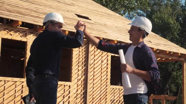 Teamwork. Konzept Gebäude Bau Architekt Zeitlupe Video. Zwei Männer in Lifestyle-Helmen schütteln sich auf einer Baustelle die Hände. team group people architekten