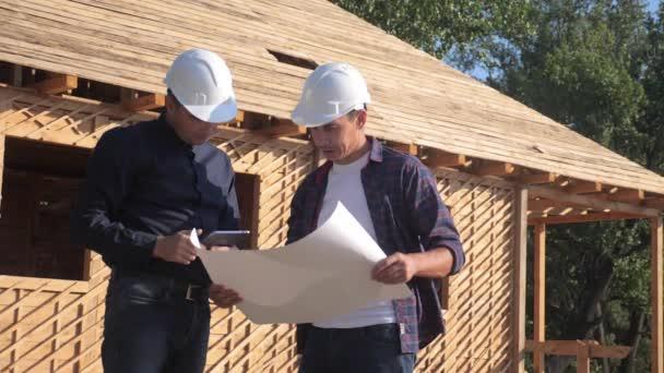 Týmová práce. koncept stavba stavba architekt pomalý pohyb videa. dva muži životní styl tvůrce v helmách potřeste rukou firemní kontrast na staveništi. Skupina tým lidé architekti