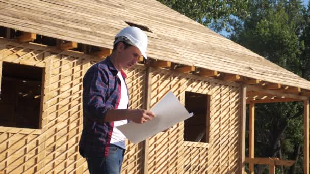 concept building constructing architect slow motion video. man builder in a helmet stands at construction holding a scheme house plan. site near a wooden frame house under construction. worker