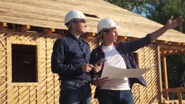 Týmová práce. koncept stavba stavba architekt pomalý pohyb videa. dva muži v helmách studují digitální tabletový plán. dva architekti pracující na stavbě stavebního domu