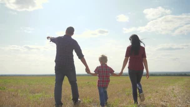 boldog családi séta természet csapatmunka barátság ellátás koncepció lassított videó. apa anyu életmód és a fia séta a természetben naplemente napfény tartsa kezét. boldog család szülei férfi és lány tartsa kisfiú