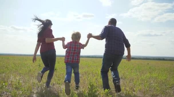 šťastná rodina provozuje přírodu teampráce přátelství péče koncept pomalý pohyb video. otec mamka a syn, kteří běží v přírodě sluneční svit se drží za ruku. šťastný rodinný rodič muž a dívka drží malého chlapce životní styl