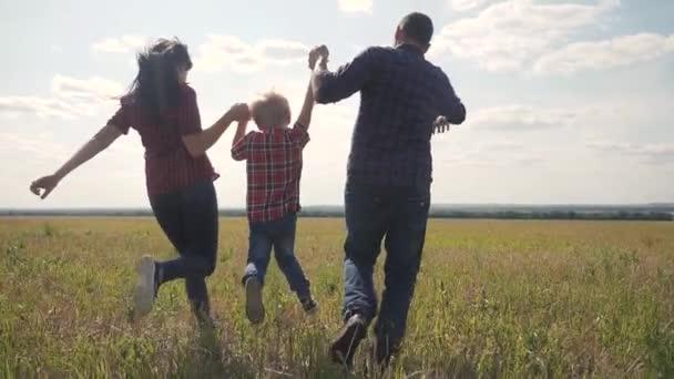 šťastná rodina provozuje přírodu teampráce přátelství péče koncept pomalý pohyb video. otec mamka a syn, kteří v přírodě běží na slunci, je životní styl ruky. šťastné rodinné rodiče muž a dívka drží málo