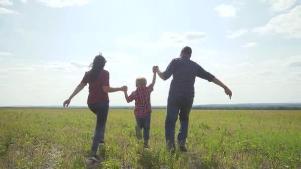 glückliche Familie betreibt Natur Teamwork Freundschaft Pflegekonzept Zeitlupe Video. Vater Mutter und Sohn, die in der Natur bei Sonnenuntergang laufen, halten sich an der Hand. glückliche Familie Eltern Mann und Mädchen Lebensstil halten kleinen Jungen