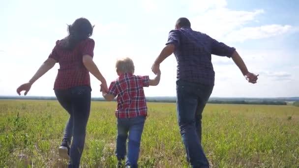 boldog család fut természet csapatmunka barátság ellátás koncepció lassított videó. apa anyja és fia fut a természetben naplemente napfény tartsa kezét. boldog életmód család szülei az ember és a lány tartsa kisfiú