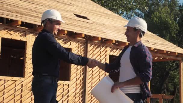 Týmová práce. koncepce výstavby architekta zpomalení videa. dva muži stavitel v helmách potřást rukou kontrast obchodní kontrast na staveništi. dva dělníci v helmách si potřásají rukama