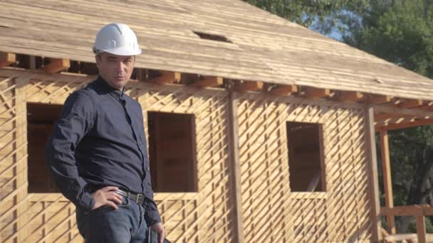 Konzept Gebäude Bau Architekt Zeitlupe Video. Bauarbeiter mit Helm steht auf der Baustelle und hält ein digitales Tablet mit einem Plan für das Haus in der Hand. Grundstück in der Nähe eines im Bau befindlichen Fachwerkhauses