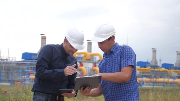 Týmová práce. Koncepce výrobních stanic zemního plynu v oboru životního stylu. video s pomalým pohybem. dva inženýři v helmách studují práci s digitálním tabletem v obchodní smlouvě o dodávkách faktérů. Dva