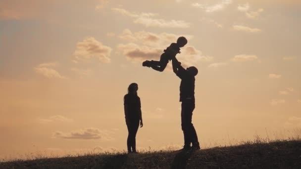 šťastné rodinné týmové práce. Veselý, veselý otec, který se baví, se rozhází ve vzdušném dítěti. otcové den. šťastný rodinný otec matka a syn životní styl silueta při slunci slunce
