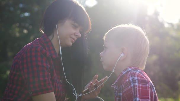 glückliche Familie lustige Zeitlupe Video Teamwork im Freien. Mutter und Sohn hören Musik auf dem Smartphone im selben Kopfhörer für zwei.