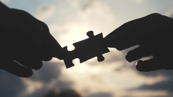 teamwork lifestyle business finance concept. male hands connect two puzzles silhouette against the sunset. teamwork symbol of association and connection. strategy business