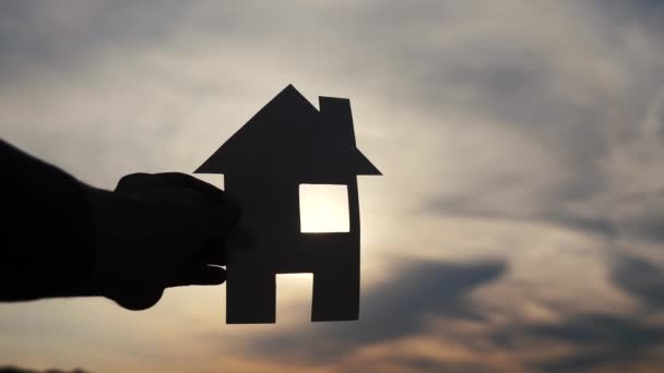 boldog családi építőház koncepció. ember tartja otthon a papírházat a kezében életmód naplemente sziluett napfény. élet-ökológia videó szimbólum
