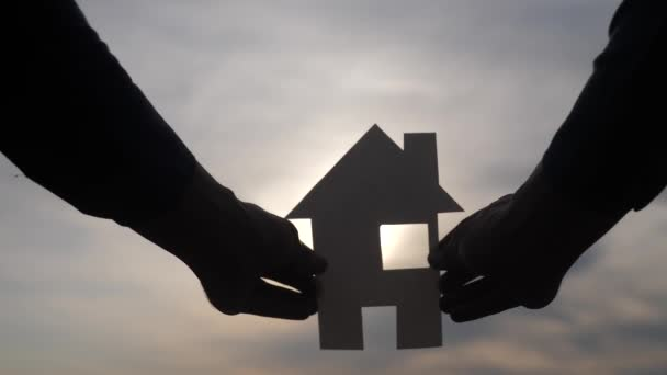 šťastný koncept rodinného stavebního domu. Muž, který drží doma papírový domek ve svých rukou při slunečním svitu siluetě. život symbol životní styl ekologie video