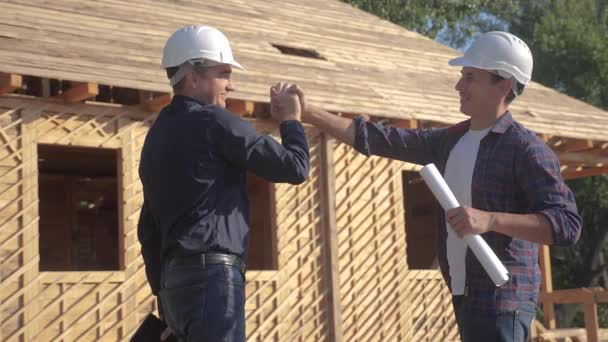 teamwork handshake. concept building constructing architect slow motion video. two men builder in helmets shake hands contract business contrast at a construction site. two workers in helmets shaking
