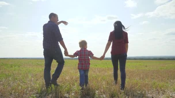 glücklich Familie Wandern Natur Teamwork Freundschaft Pflege Konzept Zeitlupe Video. Vater, Mutter und Sohn gehen in der Natur bei Sonnenuntergang Hand in Hand. glückliche Familieneltern Mann und Mädchen halten kleinem Jungen einen Spaziergang