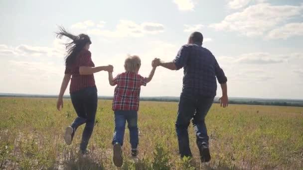 šťastná rodina provozuje přírodu teampráce přátelství péče koncept pomalý pohyb video. otec mamka a syn, kteří běží v přírodě sluneční svit se drží za ruku. šťastný rodinný rodič muž a dívka drží malého životního stylu