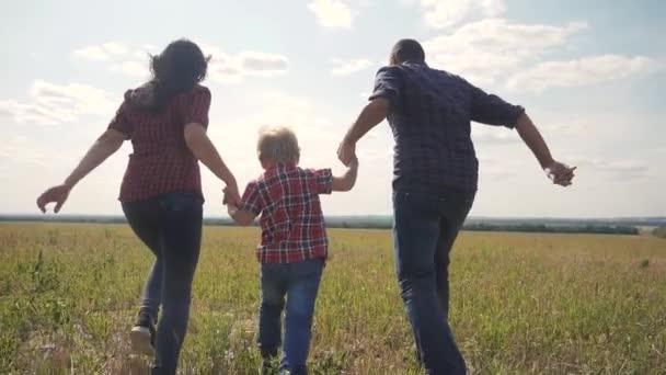 šťastná rodina provozuje přírodu teampráce přátelství péče koncept pomalý pohyb video. otec mamka a syn, kteří běží v přírodě sluneční svit se drží za ruku. šťastný rodinný životní styl rodiče muž a dívka držte malého chlapce