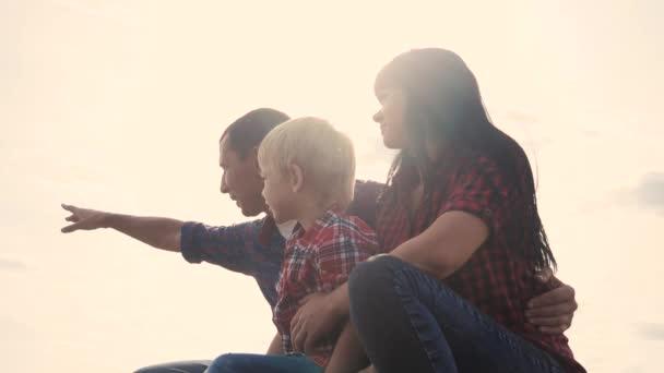 glücklich Familie Teamwork Lifestyle-Konzept Zeitlupe Video. Papa Mama und Sohn Silhouette sitzen im Freien Sonnenuntergang Sonnenlicht. Vater Mann umarmt Mutter Mädchen und Sohn zeigt Hand in die Ferne eine glückliche Familie