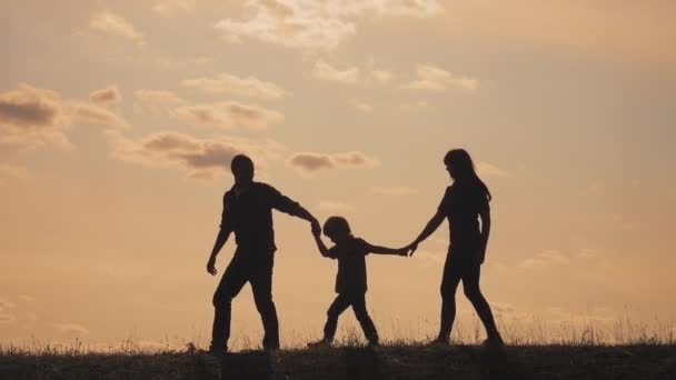 happy family teamwork. walk father, mother and son outdoors silhouette concept slow motion video. dad man mom girl hold walking little lifestyle boy son by hands. little boy jumping silhouette at