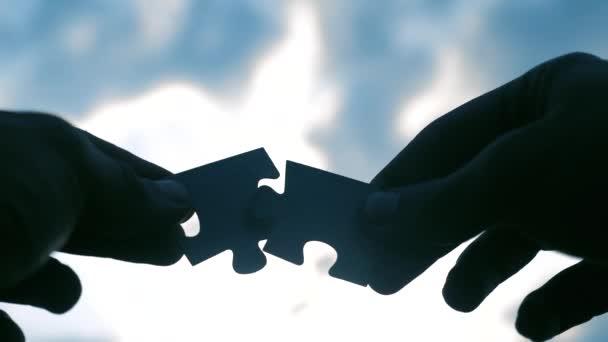 koncepce podnikových financí. mužské ruce spojují dvě hádanky s siluetou proti západu slunce. symbol týmové práce s životním stylem a připojením. strategie podnikání