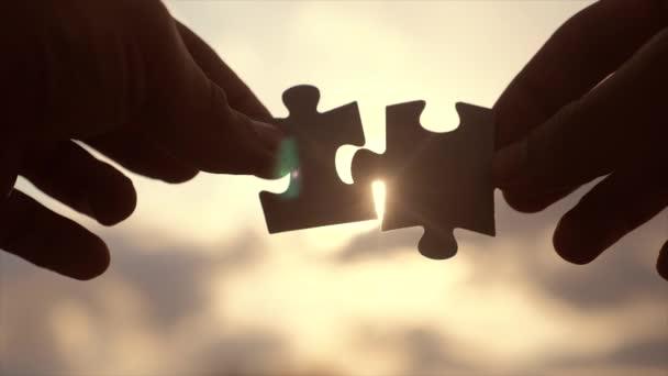 koncepce podnikových financí. mužské ruce spojují dvě hádanky s siluetou proti západu slunce. symbolem týmovém životním stylem asociace a připojení. strategie podnikání