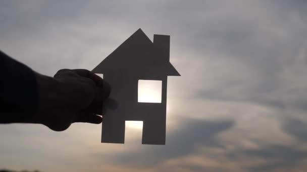 glückliche Familie Bau Haus Konzept. Mann, der bei Sonnenuntergang ein Papierhaus in der Hand hält. lebensökologisches Videosymbol