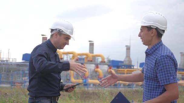 Teamwork. Industrie-Tankstellenkonzept. Zeitlupenvideo gewinnt Geschäftserfolgsstrategie. zwei Ingenieure in Helmen beim Händeschütteln über einen Gasliefervertrag. zwei Arbeiter arbeiten in der