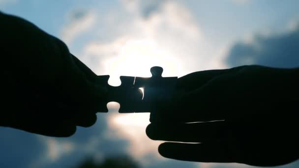 pojem životní styl pro týmové práce. mužské ruce spojují dvě hádanky s siluetou proti západu slunce. symbol týmové práce přidružení a připojení. strategie podnikání