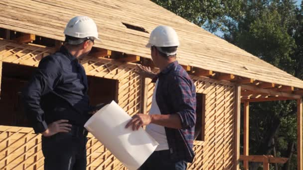 teamwork. concept building constructing architect slow motion video. two men builder in helmets study the house plan. two architects working on the construction of a frame house business contrast at