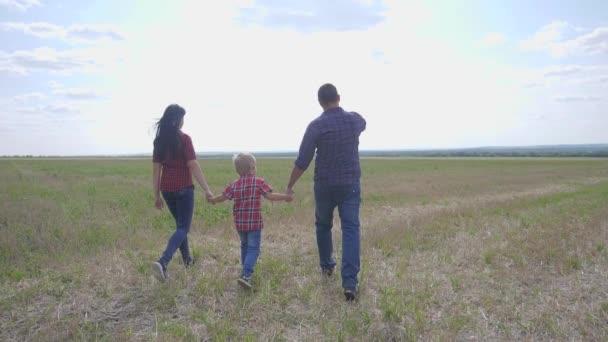 šťastný rodinný spolupracujete přátelství péče koncept pomalý pohyb video. otec mamka a syn chodí v přírodě slunce na slunci. šťastný rodinný rodič muž a dívka drží malého chlapce životní styl chůze ruka