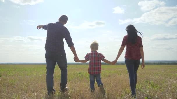 glücklich Familie Wandern Natur Teamarbeit Freundschaft Pflege Konzept Zeitlupe Video Lifestyle. Vater, Mutter und Sohn gehen in der Natur bei Sonnenuntergang Hand in Hand. glückliche Familieneltern Mann und Mädchen halten wenig
