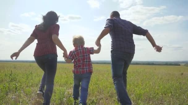 šťastná rodina provozuje přírodu teampráce přátelství péče koncept pomalý pohyb video. otec mamka a syn, kteří běží v přírodě sluneční svit se drží za ruku. šťastný rodinný rodič životní styl muž a dívka držet malého chlapce