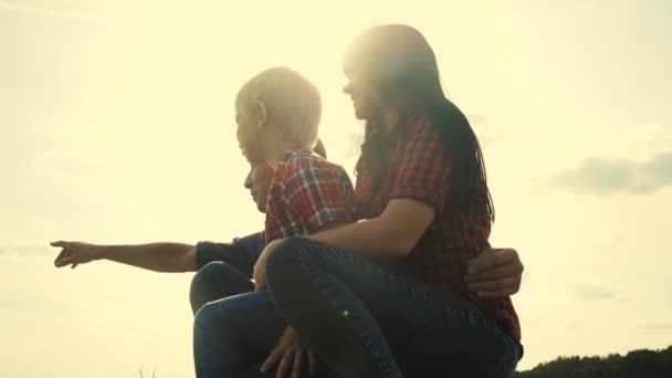 glücklich Familie Teamwork Konzept Zeitlupe Video. Papa Mama und Sohn Silhouette sitzen im Freien Lifestyle Sonnenuntergang Sonnenlicht. Vater Mann umarmt Mutter Mädchen und Sohn zeigt Hand in die Ferne eine glückliche Familie