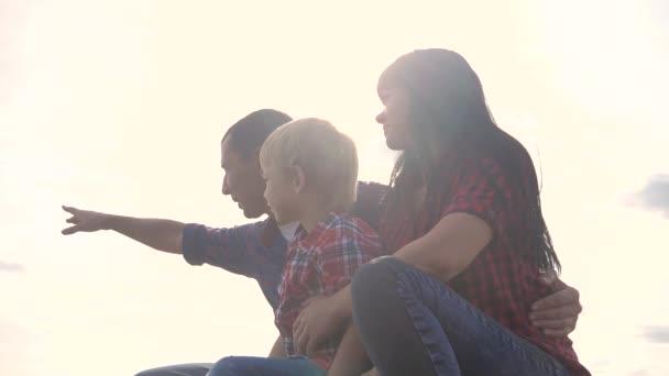 šťastný rodinný spolupracujete koncept životní styl pomalý film video. otec mamka a syn silueta sedí venku na slunci. Otče muž objetí máma a syn se v dálce ukazují, že šťastná rodina