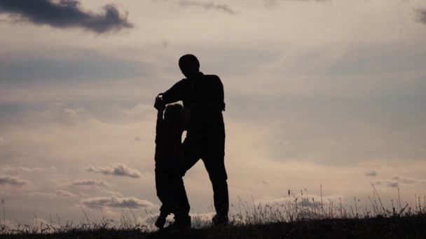 happy family funny concept teamwork father and son slow motion video. dad man and son boy silhouette swirls spinning hands silhouette at sunset. happy sweet lifestyle childhood