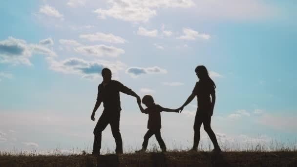 šťastné rodinné týmové práce. chodit s otcem, matkou a synem venku představa pomalého pohybu videa. táta chlap máma holka drží v rukou život malého chlapce. malý chlapec přeskakující siluetu
