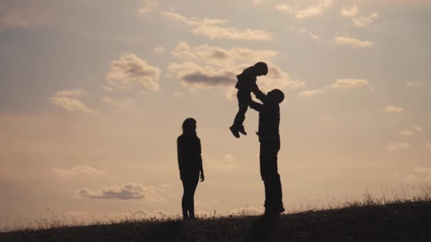 happy family teamwork. Happy joyful father having fun throws up in the air child. fathers day. happy family father mom and son silhouette at lifestyle sunset sunlight