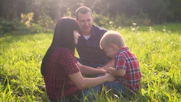 happy family teamwork outdoors concept outdoors slow motion video. mom dad and son in nature are sitting on the grass have fun. playing mom girl dad man and son boy happy lifestyle family