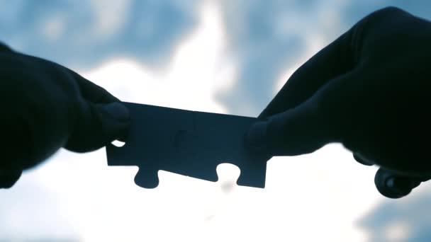 koncepce podnikových financí. mužské ruce spojují dvě hádanky s siluetou proti západu slunce. symbol životního stylu týmové práce a spojení. strategie podnikání
