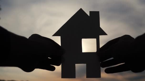 šťastný koncept výstavby rodinných domů. Muž, který drží doma papírový domek ve svých rukou při slunečním svitu siluetě. životní ekologie životní styl video symbol